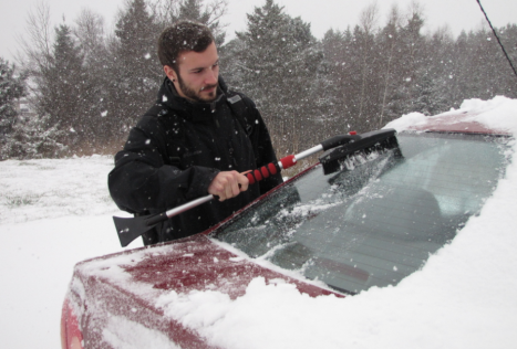 UPEI Student Matt Aucoin brushes off his car in the midst of a Dec. 10 storm on his way to a final exam. While high schools around the Island closed down early, UPEI made the decision not to delay its exams. Ryan Cooke photo.