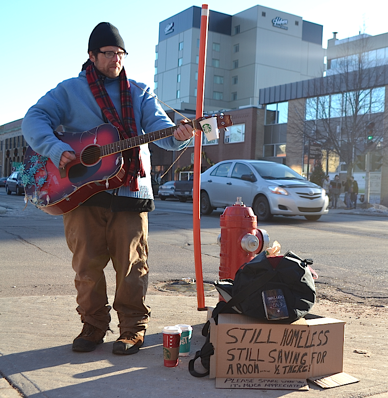 Chris Nettleton plays guitar and sings for people on the streets of Charlottetown in hopes to make enough money for a place to sleep. Jazlyn MacLeod photo.