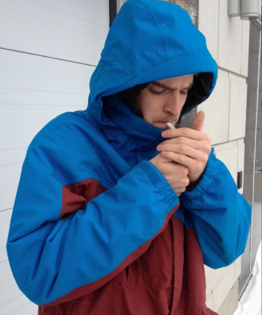 Thomas Belliveau spends several minutes looking for enough shelter to light his cigarette on Jan. 22. Brett Poirier photo.