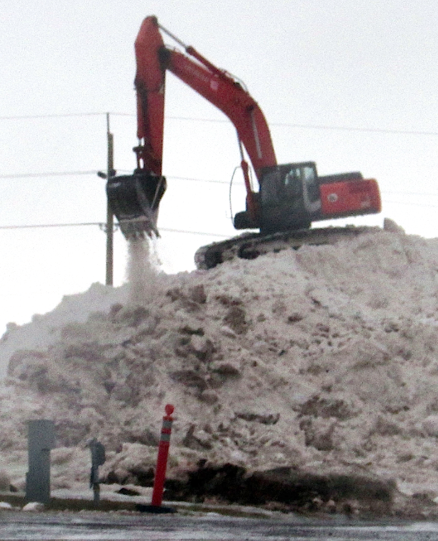 A backhoe operates on a large pile of snow at the Event Grounds in Charlottetown on Jan. 27.  Melissa Heald photo.