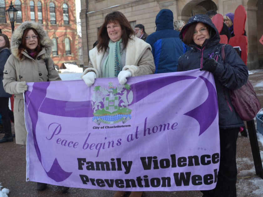 Gloria Dennis, left, Cathy McInnis, centre and Daneen MacDonald hold a banner promoting P.E.I. Family Violence Week. About 150 people braved the cold to meet at Province House for the fifth annual Walk in Silence for Victims of Violence Feb. 12. Sarah Seeley photo