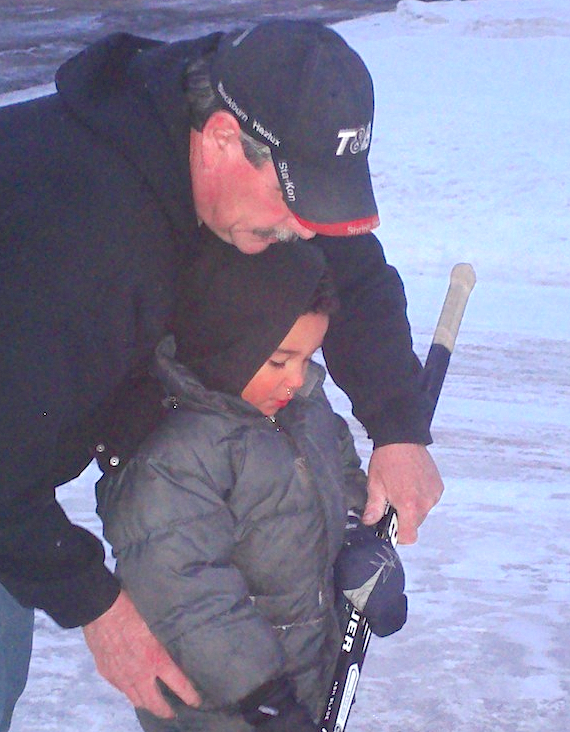 Glenn Paynter of Kensington teaches great-nephew Devonte Simmonds how to hold a hockey stick on a makeshift driveway rink after all of the freezing rain in January. Kaylynn Paynter photo.