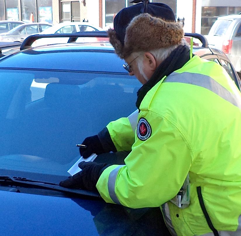 The man nobody likes to see – when he's at work, Frank Smith gives a car parked on Kent Street a ticket after its meter expires on March 7. Gwydion Morris photo.