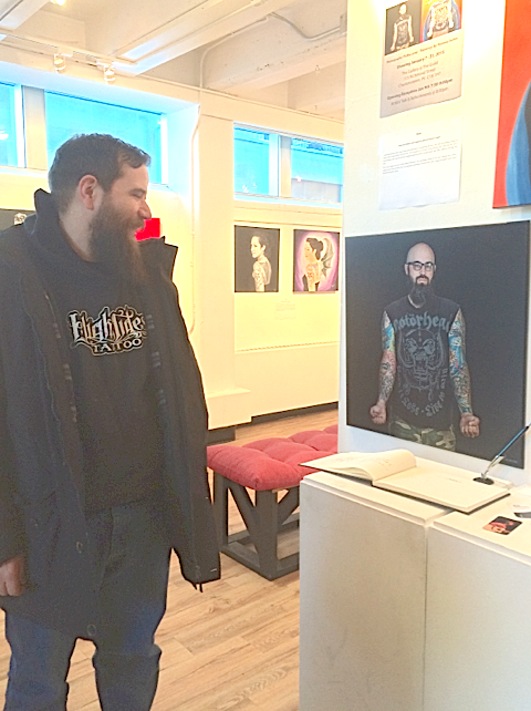 John Dohe admires the photo of a man he once tattooed. The photo is on display as part of the INK exhibit at the guild in Charlottetown. Rebecca Moase photo