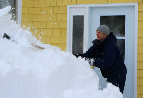 Snow removal worker Paul Coachinay breaks and pushes snow out from a front door in the middle of Charlottetown. The city has been hit hard by snowstorms in recent weeks, with 200 cm accumulated overall. James Ferguson photo.