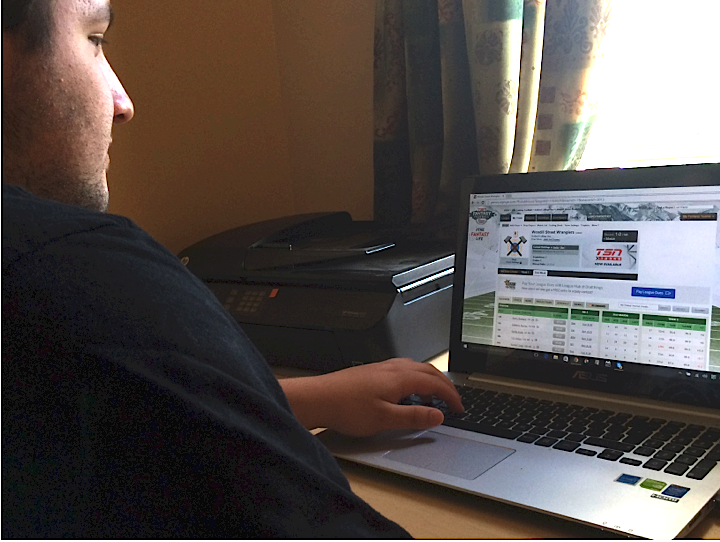 Drew Rahey, of Syndey N.S., takes one final look at his fantasy football lineup before locking it in prior to the kickoff in the Thursday night game. Ian Beauchesne photo.